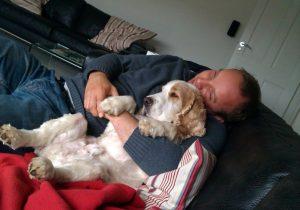 man cuddles harry on sofa