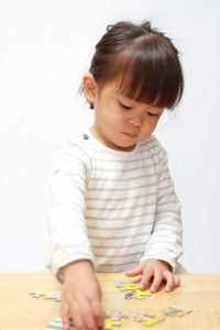 japanese girl solving jigsaw puzzle