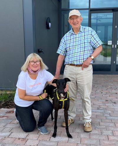 Two adopters stand with greyhound outside Dogs Trust Cardiff